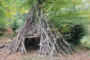 Large homemade leaning shelter of sticks outdoor education